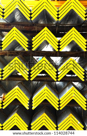 Closeup of yellow steel angles bunch in warehouse.