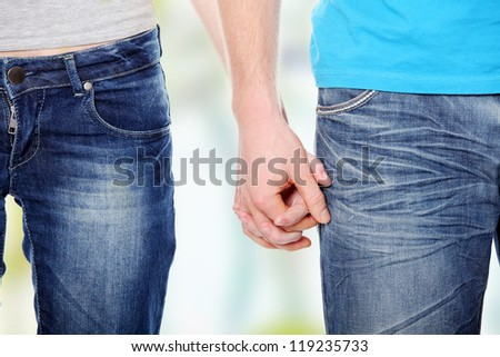 Closeup of young affectionate couple holding hands