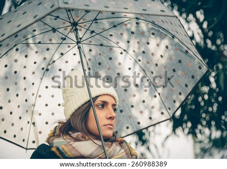 Closeup of young beautiful girl under a umbrella in an autumn rainy day