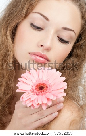 Closeup of young beautiful woman with healthy skin and long curly hair holding pink flower. Isolated on white background