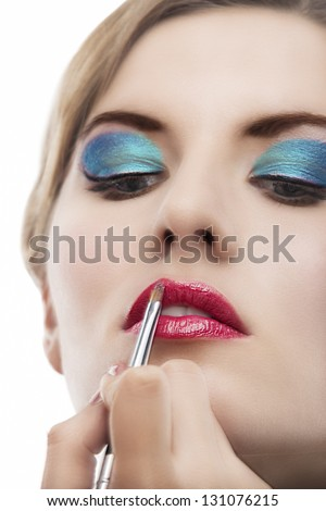 closeup of young blond caucasian girl being maked up with brush