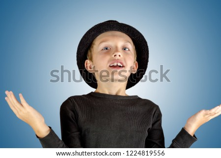 closeup of young boy in black shirt and black hat with merry smiling and litle bit surprised expression, i have said it concept #1224819556