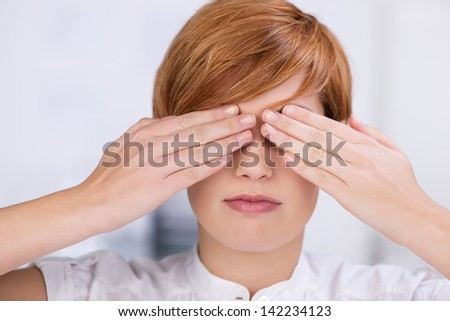 Closeup of young businesswoman covering eyes with hands in office