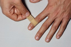 closeup of young Caucasian male hands self covering index finger with adhesive bandage on the white background
