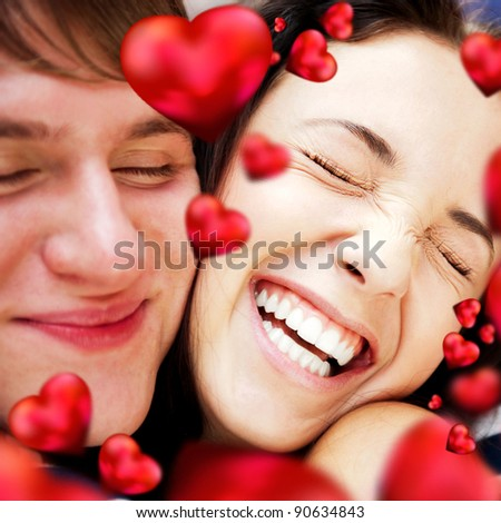 Closeup of young couple embracing and very happy to be together. Valentine concept. Red hearts are flying around them
