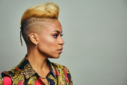 Closeup of young female hipster with short blond hair looking away against gray background
