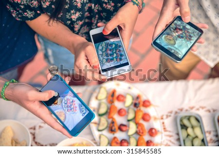 Closeup of young friends hands taking photos with their smartphones to vegetable skewers over a table in a outdoors summer barbecue