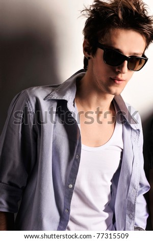 Closeup of young, handsome man thinking. Standing against wall