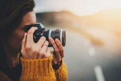 Closeup of young hipster girl taking photograph on vintage camera while standing on road capturing amazing nature landscape, traveller woman in cozy jersey enjoying vacation in Europe
