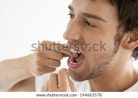 Closeup of young man flossing his teeth isolated on white background - stock photo