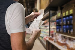 Closeup of young man holding bill to check the price in supermarket