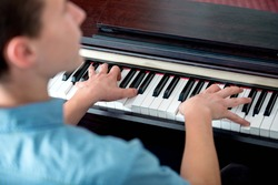 Closeup of young man playing piano from behind