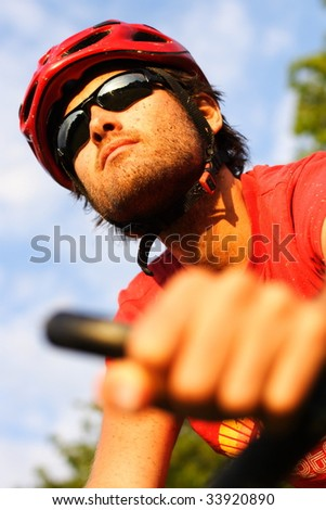 Closeup of young man riding a mountain bike in the forest on a sunny day