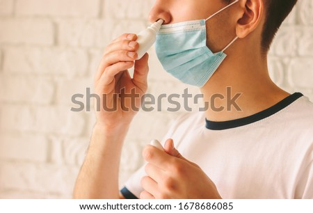 Closeup of young man with sickness using nasal spray for his congested nose. Confident ill doctor in protective medical mask on face using nose drops for runny nose. Coronavirus COVID-19 symptoms Stock photo ©