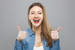 Closeup of young optimistic female isolated on grey background showing thumps up with positive emotions of content and happiness. Copyspace, concept of satisfaction with quality and recommendation.