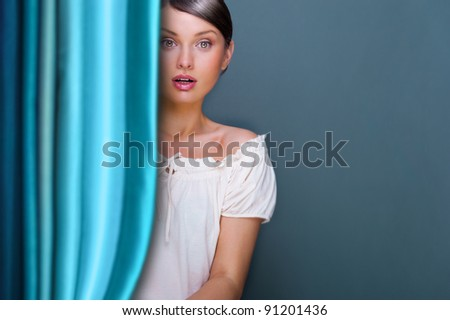 Closeup of young, pretty woman standing near curtain and holding it. Lots of copyspace for your text and logo