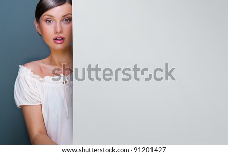 Closeup of young, pretty woman standing near huge blank board and holding it. Lots of copyspace for your text and logo
