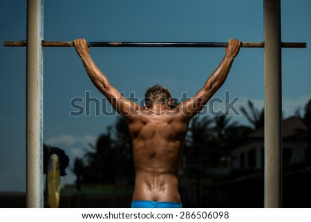 Closeup of young strong athlete doing pull-up on horizontal bar