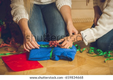 Closeup of young woman and girl wrapping sweater in decorative paper and colorful ribbons #659834668