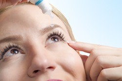 Closeup of young woman applying eye drops, selective focus only on right eye. Drop captured in mid air/ eye drops with vitamins/ eye care