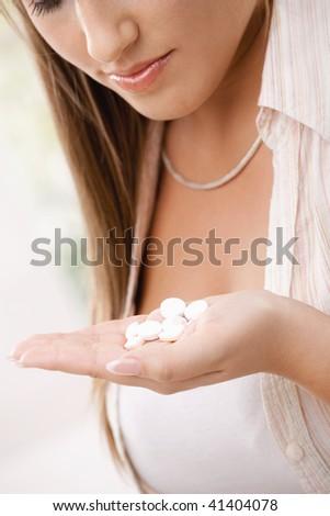 Closeup of young woman girl taking pills.