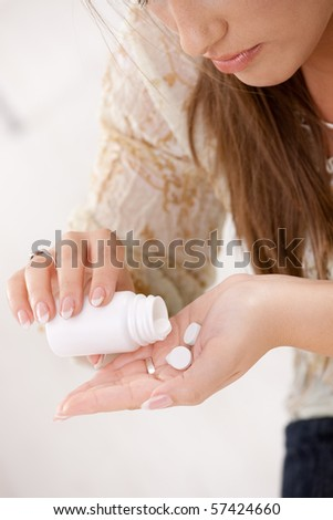 Closeup of young woman girl taking pills from bottle.