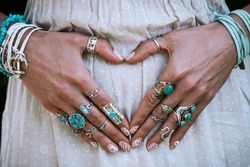 closeup of young woman hands in heart shape with lot of boho style jewelry, rings and bracelets outdoor summer day