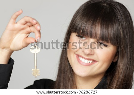 Closeup of young woman holding key isolated over gray background