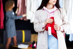 Closeup of young woman is stealing red jeans in store, shop, boutique at shopping center. Girl is hiding unpaid good under clothes. Seller, assistant caught thief on hot. Shoplifting concept.