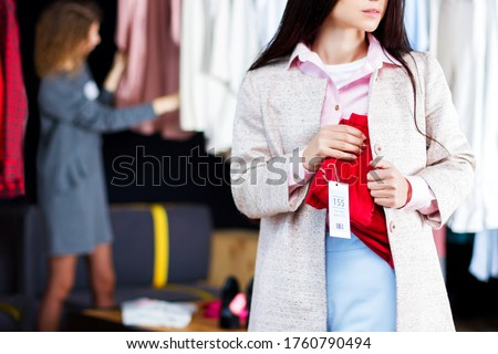 Closeup of young woman is stealing red jeans in store, shop, boutique at shopping center. Girl is hiding unpaid good under clothes. Seller, assistant caught thief on hot. Shoplifting concept. Zdjęcia stock ©
