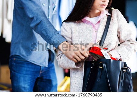 Photo of  Closeup of young woman is stealing red shoes in store, shop, boutique at shopping center. Girl is hiding unpaid good in handbag. Seller, assistant caught thief on hot. Shoplifting concept.