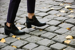 Closeup of young woman legs on Parisian cobblestone street covered with yellow autumn leaves.