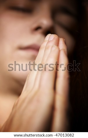 Closeup of young woman praying with folded hands and closed eyes
