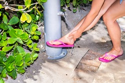 Closeup of young woman removing washing cleaning sand form legs under shower with water drops spraying over feet in Sunny Isles Beach Miami, Florida