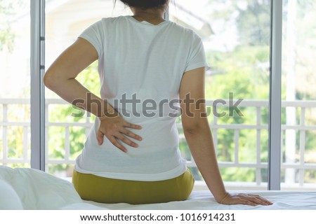 Closeup of young woman suffering from pain kidney disease while sitting on bed at home, Healthcare And Medicine concept