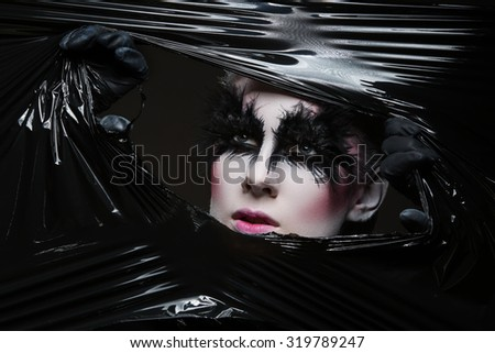 Stock Photo Closeup of young woman with feathers eyelashes tearing apart black polyethylene film and looking through it