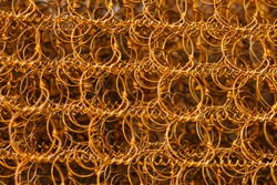 Closeup old and rusty bed coil spring, orange color rusted metal steel suspension for mattress