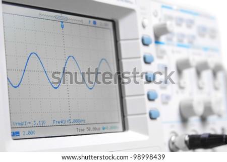 Closeup on a digital oscilloscope showing a sinusoidal waveform #98998439