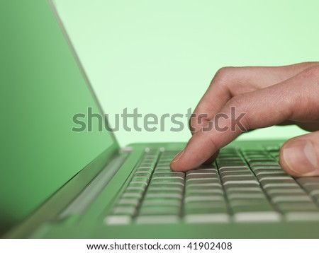 closeup on a hand writing on a laptop keyboard