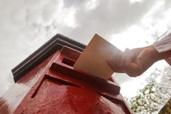 Closeup on a male hand putting a letter in a red letterbox. Concept of vintage type of communication. To send postcard from vacation or travel
