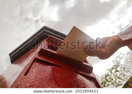 Closeup on a male hand putting a letter in a red letterbox. Concept of vintage type of communication. To send postcard from vacation or travel Stock photo ©