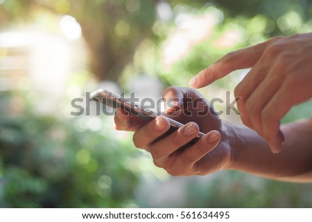 Closeup on a man's hands as he is using a smart phone.