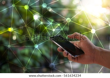 Closeup on a man's hands as he is using a smart phone.There is a social network image in the foreground.