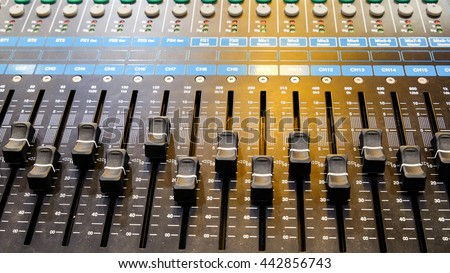 Closeup on a sliders of a mixing console. It is used for audio signals modifications to achieve the desired output. Applied in recording studios, broadcasting, television and film post-production.