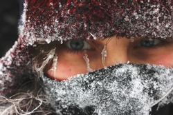 Closeup on a woman's frozen face. Icy face. Woman in winter. Face covered with ice.