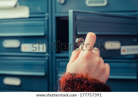 Closeup on a woman's hand as she is getting her post out of her letterbox #177757391