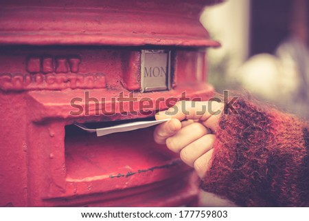 Closeup on a woman\'s hand as she is posting a letter