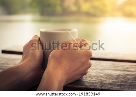 Closeup on a woman's hands holding a cup of tea by a lake in the afternoon