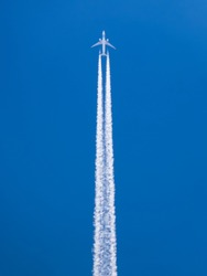 Closeup on airplane contrail against clear blue sky