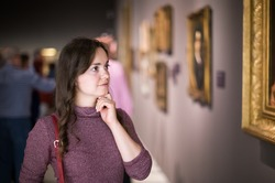Closeup on attentive woman visiting museum and enjoying arts